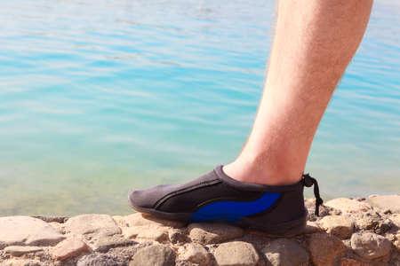 neoprene: Water swimming shoe in Pink neoprene on rocks in water on beach. Stock Photo