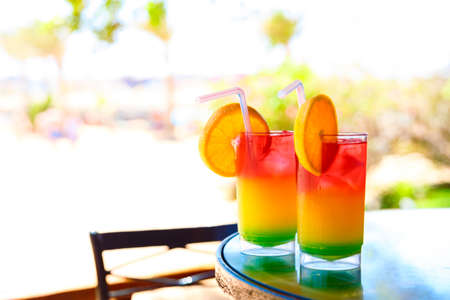 longdrink: Two bocals of colorful cocktail on a beach table near ocen.
