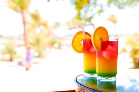 relaxen: Two bocals of colorful cocktail on a beach table near ocen.