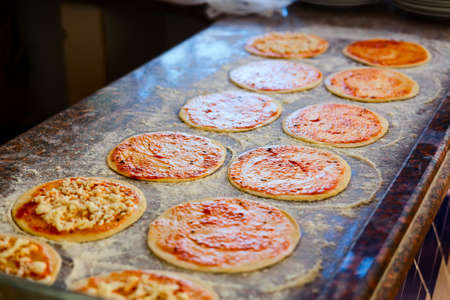 pizza base: adding tomato sauce to pizza base in arabic restaurant