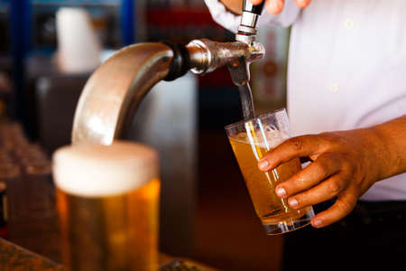 beer tap: Draft beer pour in a glass from the crane Stock Photo