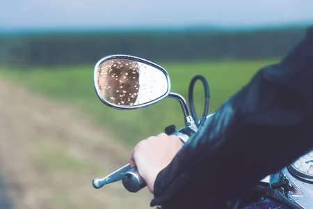 mirror: Reflection of Motorcycle Driver in Rearview Mirror