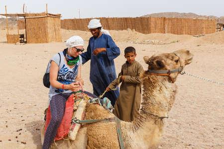 camello: HURGHADA, Egipto - el 18 de mayo 2015: Niño árabe, un residente de los rollos de la aldea beduina de los turistas de dinero en un camello. Editorial