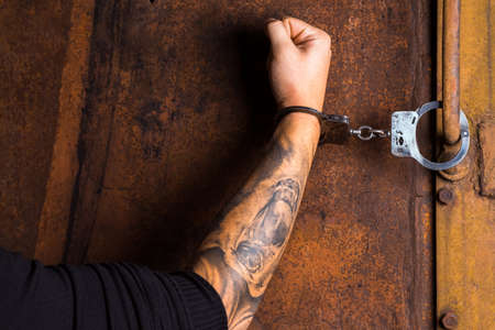 goon: Tattooed hand of a criminal handcuffed. Close up. Stock Photo