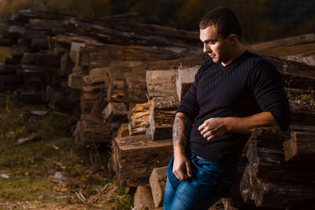 indoors: casual young man with tattoo standing indoors