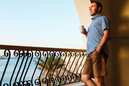 handsome guy standing on balcony in luxury hotels in Egypt at sunset and drinking tea.