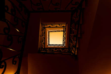three story: Looking down a three story staircase in ancient building Stock Photo