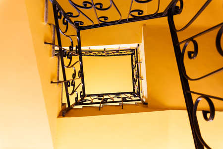 bannister: Looking down a three story staircase in ancient building Stock Photo