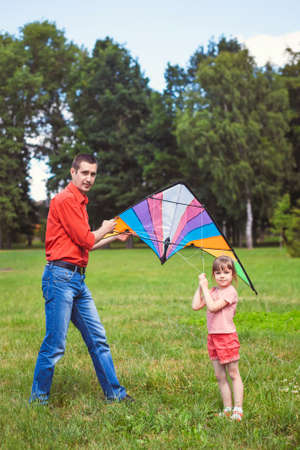 kite: The girl and her father play with a kite. Dad devotes time to the child. Stock Photo