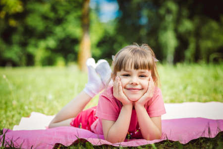 grandkid: Happy girl lying in Park on blanket Stock Photo