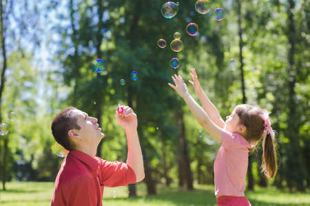 blue bubbles: A dad and his daughter are making bubbles in the park Stock Photo