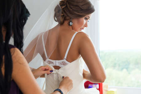 white dresses: Bride dressing gown. Bride preparing for a wedding. Bride is getting dressed in the room. Young bride prepare for the event by makeup artist.