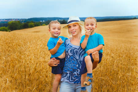 hay field: Young mother and two little twins kid boys having fun on yellow hay field in summer. Stock Photo