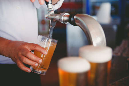 bartender: Draft beer pour in a glass from the crane Stock Photo