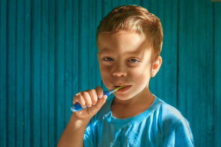 romp: Boy cleaning teeth on wooden blue background