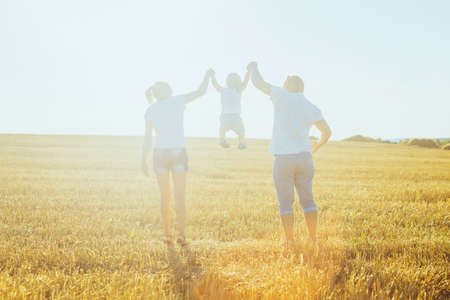 happy family at sunset walking on a field