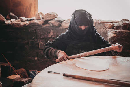 HURGHADA, EGYPT - MAY 18, 2015: Old Arab woman prepares bread in a Bedouin village