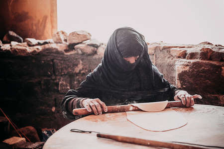 bedouin: HURGHADA, EGYPT - MAY 18, 2015: Old Arab woman prepares bread in a Bedouin village