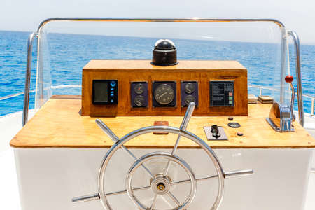 without people: Sailing yacht control wheel and navigation implement. Horizontal shot without people