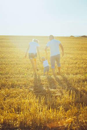 Famiglia felice al tramonto camminare su un campo Archivio Fotografico - 45289598