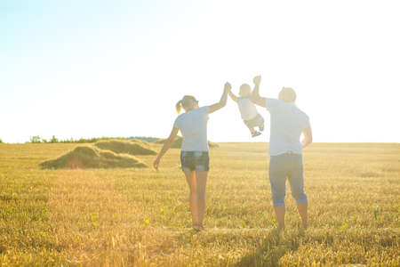 lifestile: happy family at sunset walking on a field