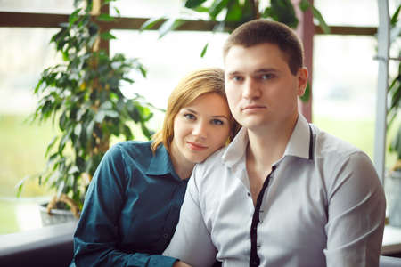 caf: Couple sitting in cafe and looking in camera