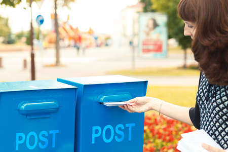 mailbox: A woman puts letters in the mailbox to send Stock Photo