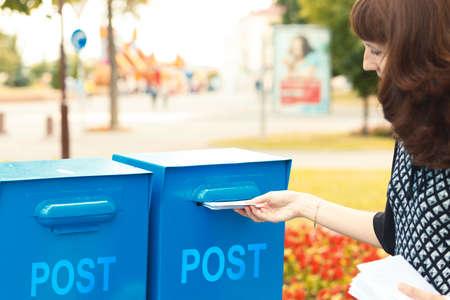 buzon: Una mujer pone las cartas en el buzón de correo para enviar