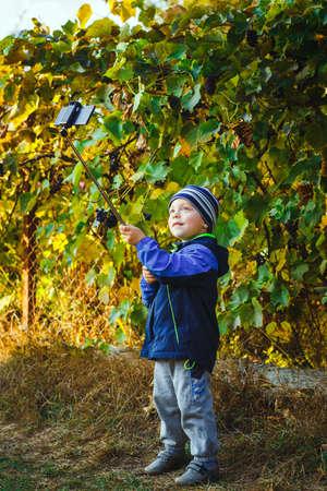 country boy: smart happy little boy taking selfie stick picture