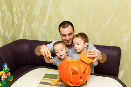 Young father and two his sons making jack-o-lantern pumpkin for halloween in kitchen