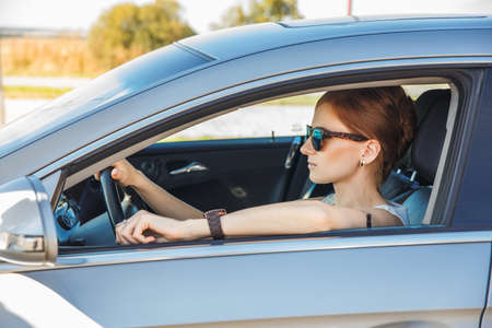 red haired woman: Beautiful red haired woman driving a car