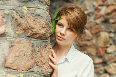 observing: Young smiling woman observing behind stone wall Stock Photo