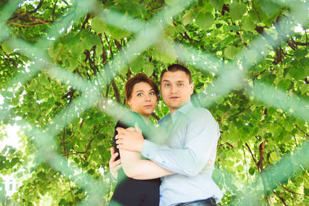 enamorados besandose: Dos amantes que se besan en el parque detrás de la valla Foto de archivo