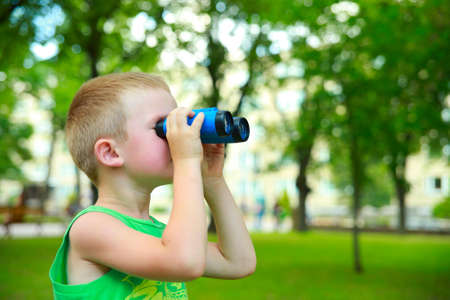 camp: Boy looking through Binoculars in city park