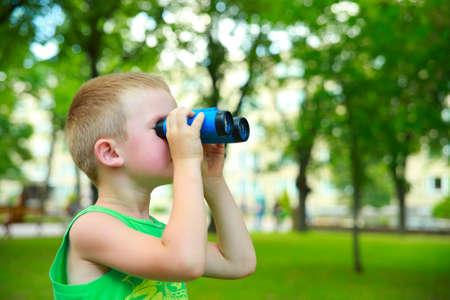 campamento: Niño mirando a través de los prismáticos en el parque de la ciudad