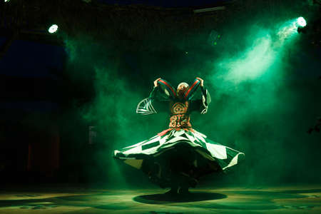 spins: HURGHADA, EGYPT - MAY 18: A Sufi dancer spins with a drums during a national egyptian dance on tourist show near by Hurghada, Egypt on May 18, 2015