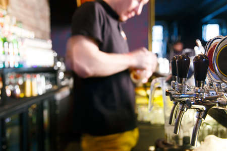 non alcoholic beer: young man working as a bartender in a nightclub bar Stock Photo