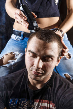hair studio: Young punk girl cuts her boyfriend using clippers.