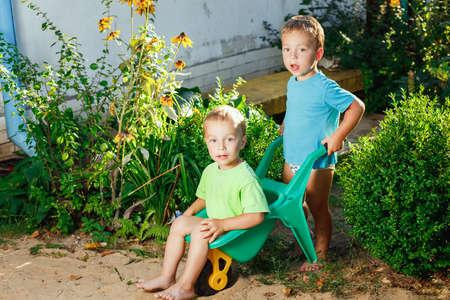 hermanos jugando: hermanos gemelos que juegan usando un carritos de jard�n Foto de archivo
