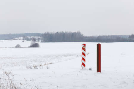 crossings: Boundary pillars of Belarus and Poland on the border in a winter field