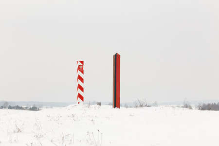 smuggling: Boundary pillars of Belarus and Poland on the border in a winter field