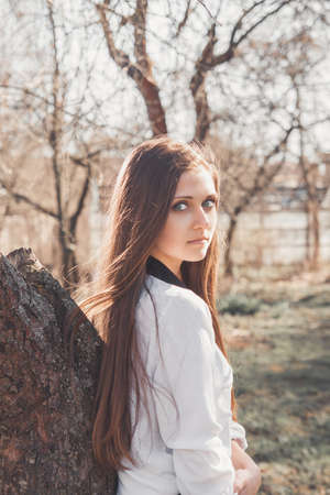 captivating: Beautiful girl in spring garden standing near by tree