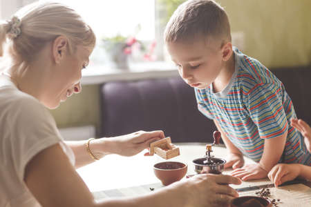 grind: Twin brothers helping her mother to grind coffee in the kitchen in the morning. Stock Photo