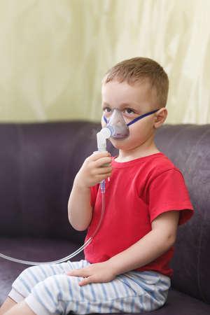 inhalation: Small boy does therapeutic inhalation using a nebulizer Stock Photo