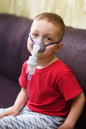 inhalation: Small boy does therapeutic inhalation using a nebulizer Stock Photo