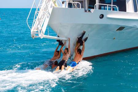 departing: YALTA, UKRAINE- JULY 09, 2012: Teenagers having fun, clinging to a departing pleasure boat Editorial