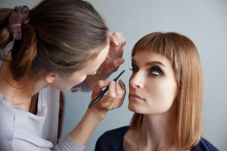pesta�as postizas: artista de maquillaje de las pesta�as falsas encola a la mujer hermosa joven