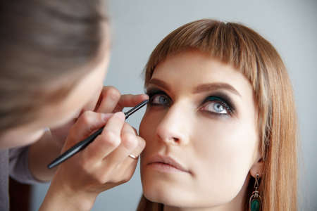 pestaÑas postizas: makeup artist glues false eyelashes to young beautiful woman
