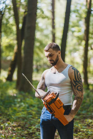 woodworker: portrait of aggressive muscular male lumberjack, woodworker with chainsaw in hand, posing Stock Photo