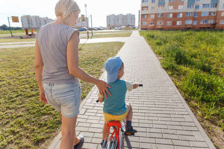 2 3 years: Mom helps son to ride a Bicycle for the first time